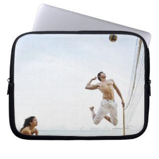 Pares que juegan a voleibol de playa en seis senti funda ordendadores