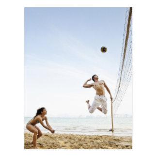 Pares que juegan a voleibol de playa en seis senti postales