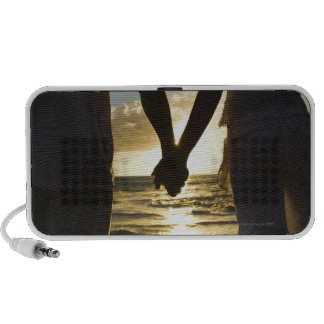 Pares que llevan a cabo las manos en la playa en l laptop altavoces