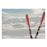 Pares rojos de esquí que se colocan en nieve mantel