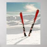 Pares rojos de esquí que se colocan en nieve póster