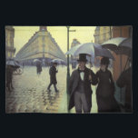 """Paris Street Rainy Day by Gustave Caillebotte Placemat<br><div class=""""desc"""">Paris Street, Rainy Day (aka Paris: A Rainy Day) (1877) by Gustave Caillebotte is a vintage impressionism fine art urban cityscape painting. A cobblestone street intersection near the Gare Saint-Lazare, a railroad train station in north Paris, France. People are walking in the rain holding umbrellas in the city. About the...</div>"""
