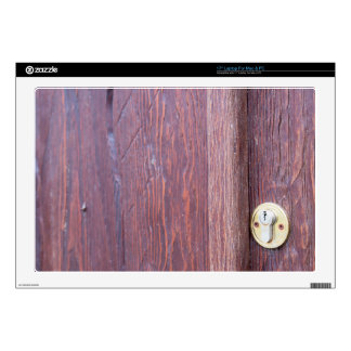 """Part of the wooden door brown close-up with brass 17"""" laptop decal"""