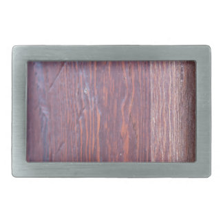 Part of the wooden door brown close-up with brass belt buckle