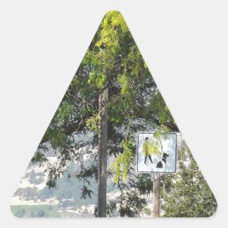 Paseo del mascota con los árboles pegatina triangular