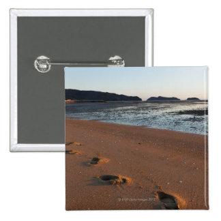 Pasos en las arenas en la salida del sol pin cuadrado