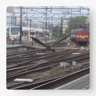 Passenger Trains arriving at railway station clock