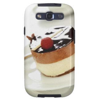 Pastel de queso adornado en la placa con la taza d galaxy SIII coberturas