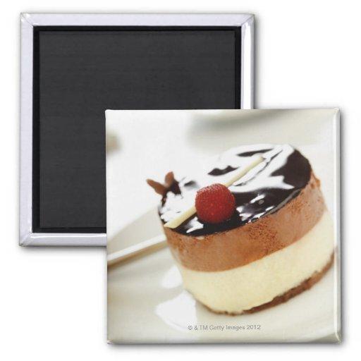 Pastel de queso adornado en la placa con la taza d imán de frigorifico