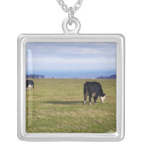 Pastoral scene of cows in field overlooking silver plated necklace