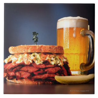 Pastrami sandwich with mug of beer large square tile
