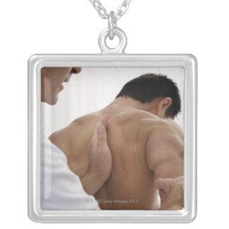 Patient receiving osteopathic treatment square pendant necklace