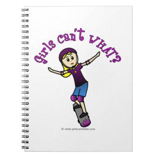 Patinador ligero del chica con el casco libros de apuntes con espiral