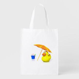 Pato de goma en la playa bolsa de la compra