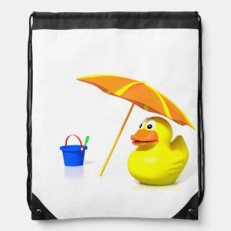 Pato de goma en la playa mochilas