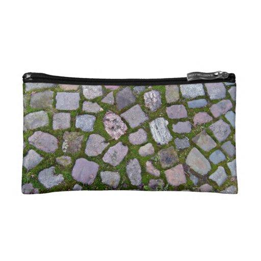Pavimento de piedra viejo con el musgo y la hierba