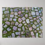 Pavimento de piedra viejo con el musgo y la hierba impresiones