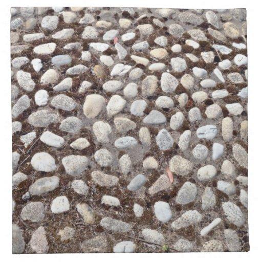 Pavimento del guijarro y plantas verdes servilleta imprimida