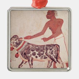 Peasant leading a cow to sacrifice metal ornament