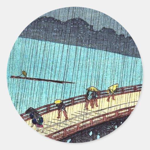 Peatones que cruzan un puente durante una tormenta pegatina redonda