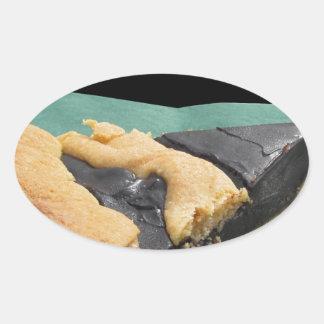 Pedazo de torta de chocolate y de pastel de queso pegatina ovalada