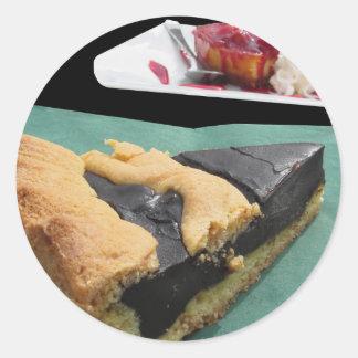 Pedazo de torta de chocolate y de pastel de queso pegatina redonda