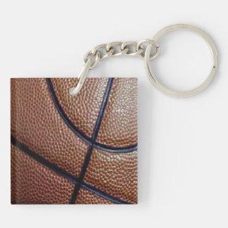 Pedazo de un baloncesto con los hoyuelos y las llavero cuadrado acrílico a doble cara