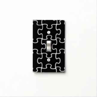 pedazos blancos y negros del rompecabezas cubiertas para interruptor