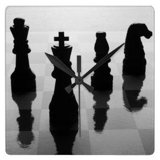 Pedazos de ajedrez en tablero de ajedrez en blanco reloj cuadrado