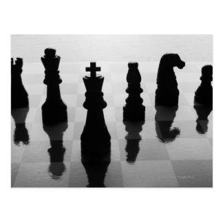 Pedazos de ajedrez en tablero de ajedrez en blanco tarjeta postal