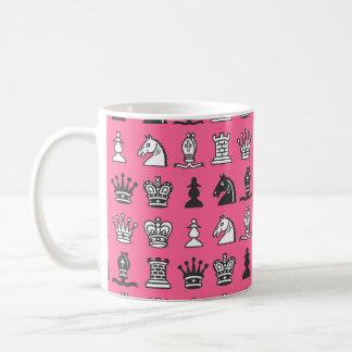 Pedazos de ajedrez en taza rosada de las filas