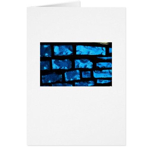 Pedazos de cristal azules con lechada negra entre tarjeta de felicitación