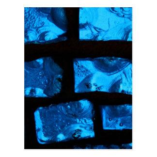 Pedazos de cristal azules con lechada negra entre tarjetas postales