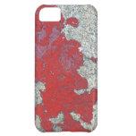 Peladura de la pintura roja contra el cemento