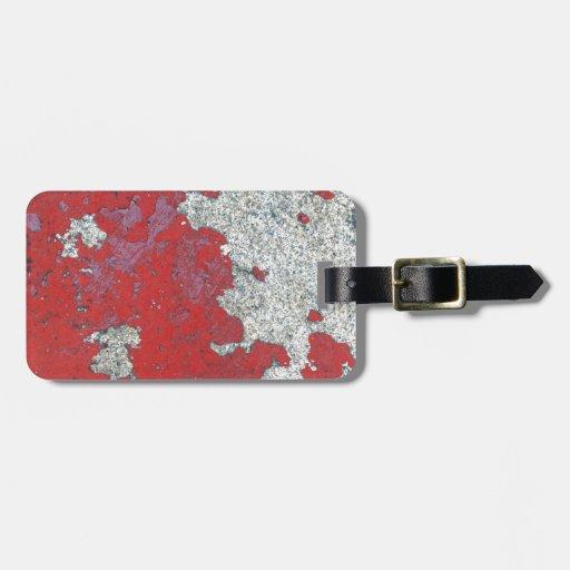 Peladura de la pintura roja contra el cemento etiquetas para equipaje
