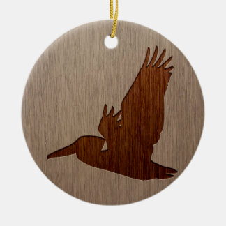 Pelican silhouette engraved on wood design ceramic ornament