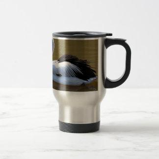 Pelican swimming on river travel mug