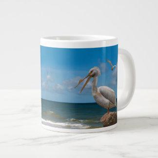 Pelícano blanco en una roca tazas jumbo