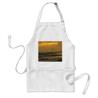 Pelicans flying over ocean waves during sunrise adult apron