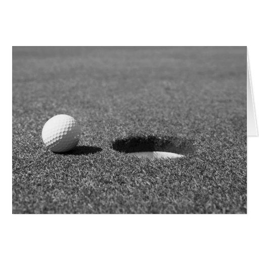 Pelota de golf al lado del agujero felicitación