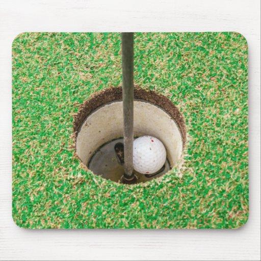 Pelota de golf en agujero tapete de raton