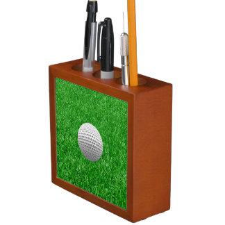 Pelota de golf en césped portalápices