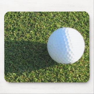 Pelota de golf en el cojín de ratón del verde del  tapete de ratones
