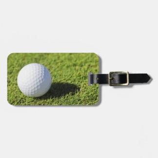 Pelota de golf en el curso de la hierba verde - mo etiquetas para equipaje