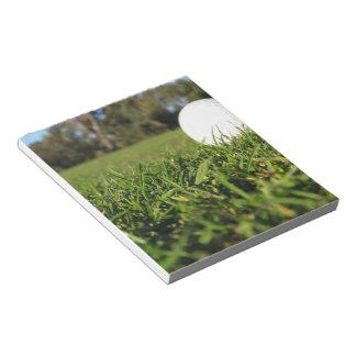 Pelota de golf en la libreta del curso bloc