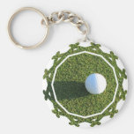 Pelota de golf en llavero del verde del golf