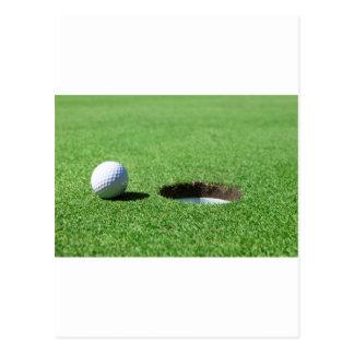 Pelota de golf y agujero postal