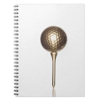 Pelota de golf y camiseta del oro libro de apuntes