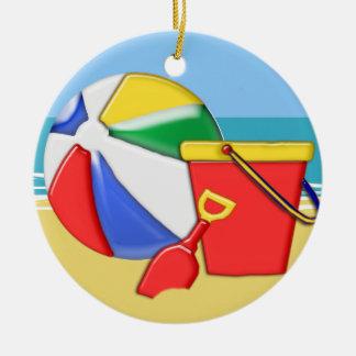 Pelota de playa, cubo y pala en la orilla adorno navideño redondo de cerámica