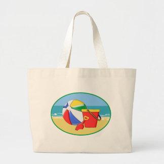 Pelota de playa, cubo y pala en la orilla bolsas
